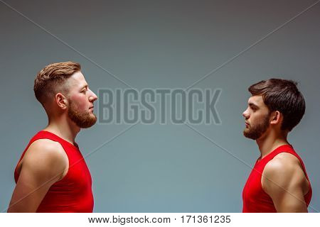 The two gymnastic acrobatic caucasian men posing in on gray studio background profile
