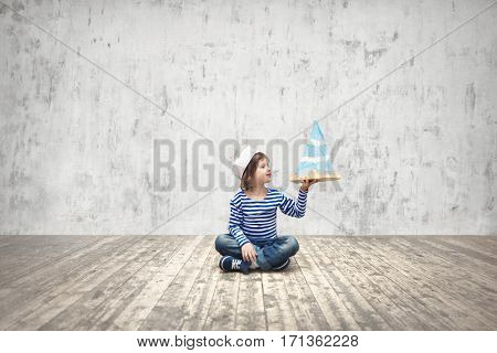 Smiling kid with ship indoors