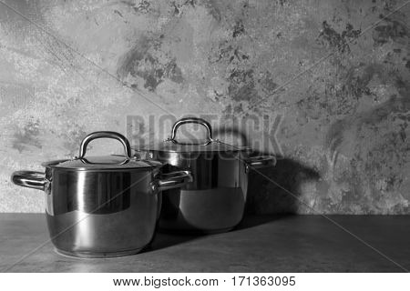 Metal pans with lids on textured wall background