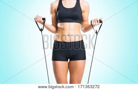 Fit, healthy and sporty woman in sportswear doing expander exercise over cyan background.