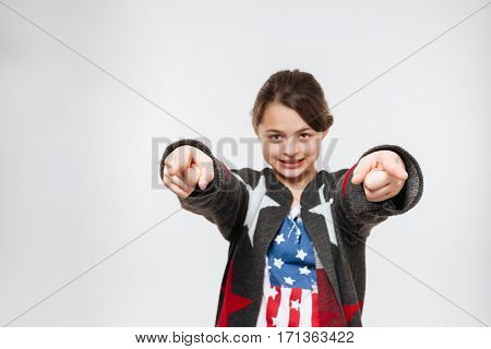 Smiling young girl in clothes in the form of American flag pointing at camera. Isolated gray background