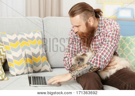 Young bearded man with fluffy cat on lap using laptop