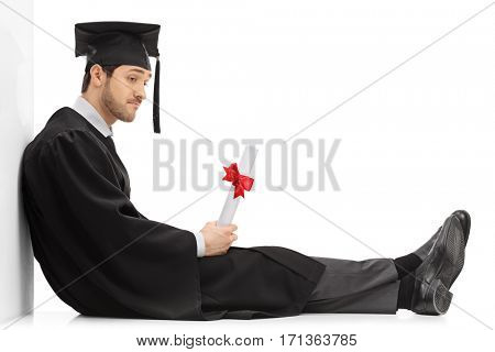 Sad graduate student with a diploma sitting on the floor and leaning on a wall isolated on white background