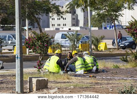 JORDAN, AQABA - 8 JANUARY 2017: Construction workers resting on the street at lunchtime: JANUARY 12, 2017 in Jordan. Aqaba