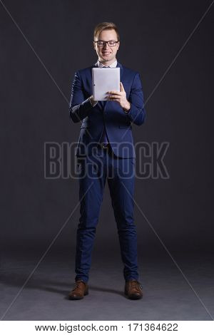 Young and confident business man. Businessman in suit over dark background.