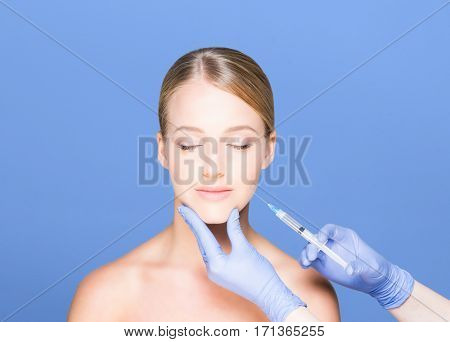 Doctor making injections in a beautiful face of a young woman over blue background. Plastic surgery concept.