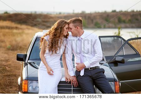 bride and groom sit on the hood of the car and look at each other