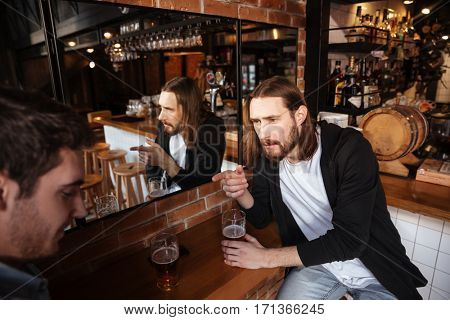 Side view of drunk friends sitting near the mirror with cups of beer in cafe