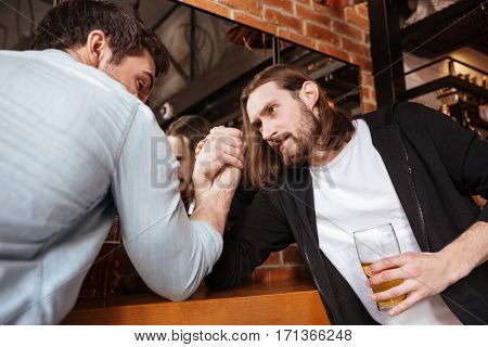 Drunk friends playing in arm wrestling near the mirror in cafe poster