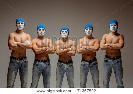 The group of caucasian men in white masks and hats, jeans posing on gray studio background
