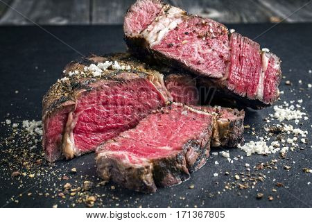 Barbecue dry aged Kobe Rib Eye Steak as close-up on a black slate
