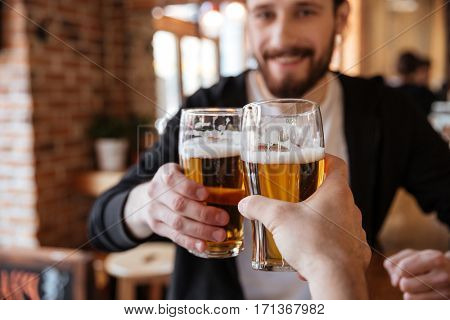 First view of man clinking glasses with friend on bar. Focus on cups.