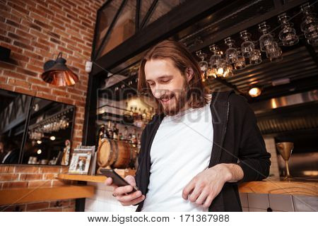 View from below of bearded man standing on bar with phone