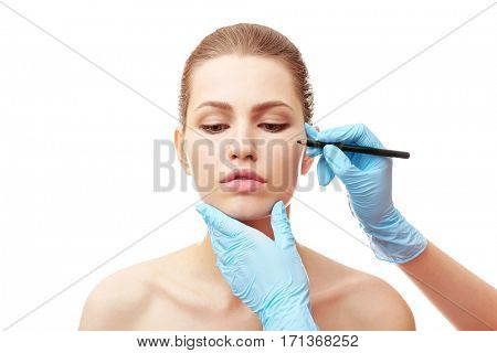 Plastic surgeon drawing line on female face, on white background