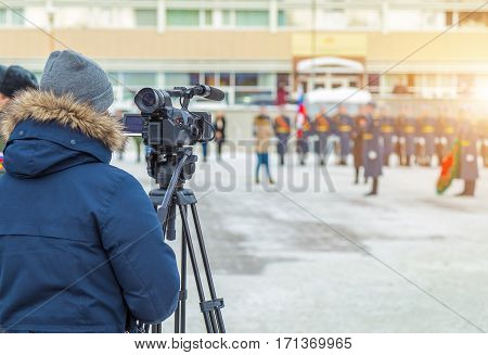 Cameraman shooting a military parade in the winter