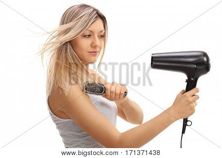 Pretty young woman using a hairbrush and a hairdryer isolated on white background