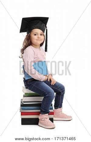 Little girl with a graduation hat sitting on a pile of books isolated on white background