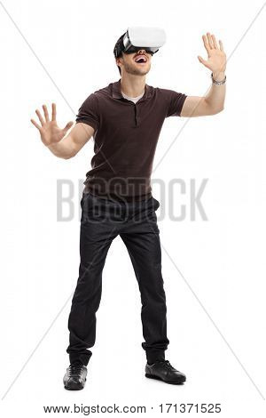 Full length portrait of an amazed man experiencing virtual reality through a headset isolated on white background