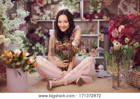 Beautiful girl in tender pink dress with bouquet flowers peonies in hands sitting on table against floral background in flower shop. Joyful asian female florist. Playful fashion model looking at camera.