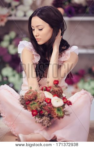 Beautiful girl in tender pink dress with flowers peonies in hands sitting on table against flower background in flower shop. Sad asian female florist. Serious fashion model looking away.