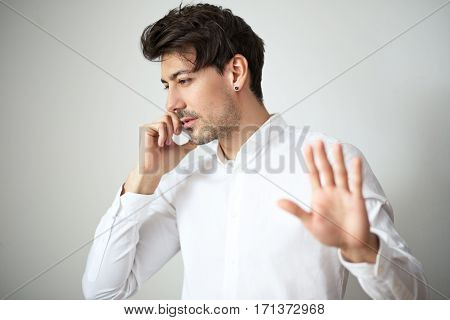 young handsome man in white shirt talking on cell phone posing in photostudio next to the color background