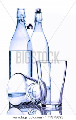 Bottles and glass of water on white background