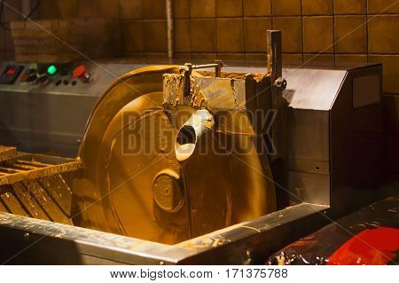 Machine processes and creation of chocolate in dark room. Pouring chocolate. Machine control buttons