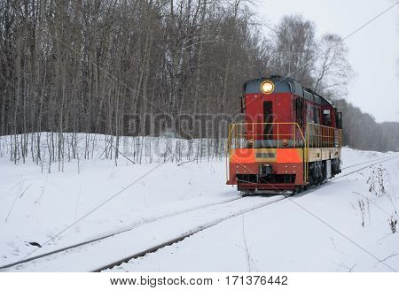 Old locomotive rides alone on the railroad in winter forest