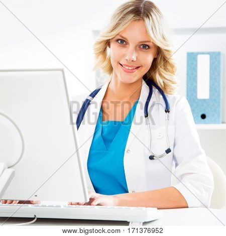 Female doctor sitting at the desk with computer