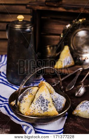 Triangular cookies with poppy seeds and powdered sugar. Selective focus.