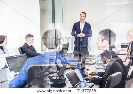 Successful team leader and business owner leading business meetingin corporate office. Business people working on laptops in foreground and glass reflections. Business and entrepreneurship concept.