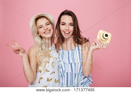 Two cheerful lovely young women standing and holding photo camera over pink background