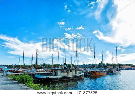 Picture of row sailboats reflected in water, yacht port on the bay, water transport, beautiful vessel in the harbor, summer vacation, active lifestyle, holiday concept