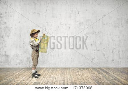 Little boy in uniform with a map