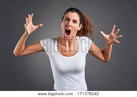 Portrait of a beautiful young woman screaming furiously.