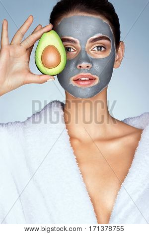 Pretty girl holding half an avocado in front of her face. Photo of girl in white bathrobe and with mask of clay on face. Grooming himself