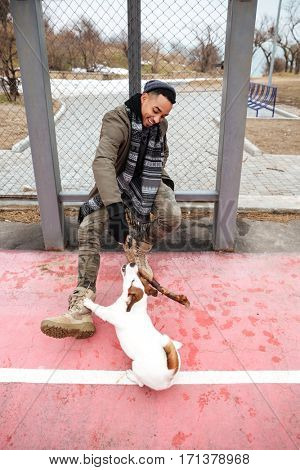 Happy african american young man smiling and playing with dog outdoors