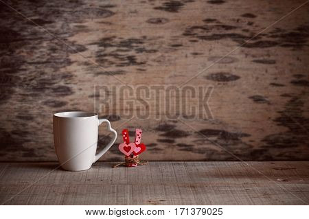 Cup of coffee and heart with love on the old wooden floor.