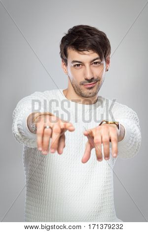 half length portrait of young smiling man pointing fingers wearing white pullover standing next to color background