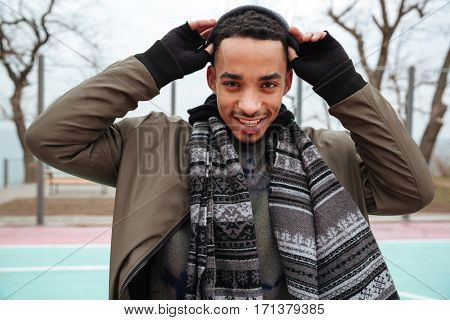 Smiling african american young man standing and taking on his hat outdoors