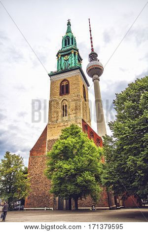 BERLIN GERMANY - JUNE 6 2012: Berlin TV Tower with St. Mary's Church in central Berlin near Alexanderplatz