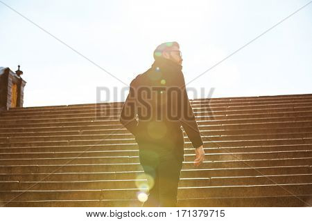 Back view of attractive young man walking on stairs outdoors