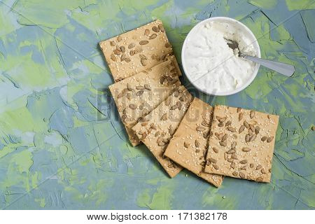 Homemade wholegrain crackers with sesame sunflower seeds and cream cheese with fresh herbs on blue-green textured background. The concept of diet and healthy eating. Top view