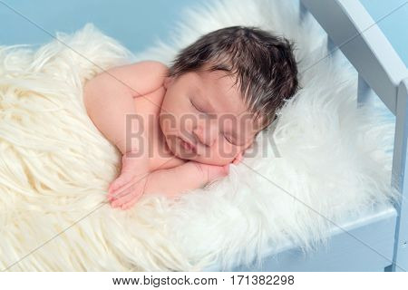 Tranquil infant sleeping on his side, covering himself with a white blanket, closeup