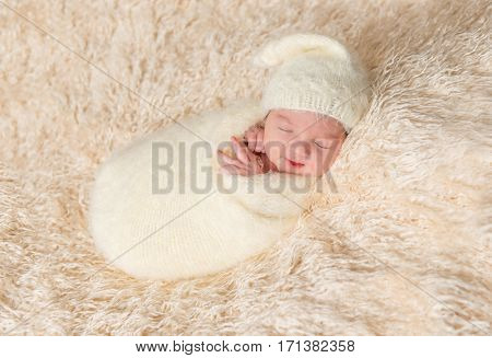 Newborn in a hat sleeping oh his side, enveloped in a soft white blanket
