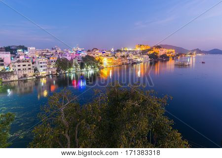 Glowing Cityscape At Udaipur At Dusk. The Majestic City Palace Reflecting Lights On Lake Pichola, Tr