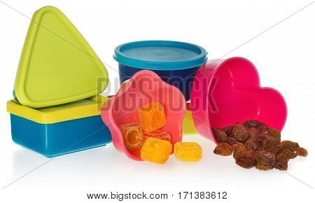 Multi colored kitchen molds with raisins and candy. Box closed in the shape of heart star asquare and a circle. Containers in the colors blue dark blue yellow pink red. cookie cutters on a white background with slight reflection.