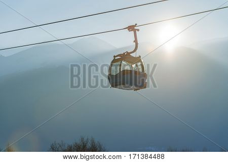 Ropeway and cable car transport system for skiers in sunset