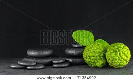 Spa Concept Of Bergamot Fruit And Zen Basalt Stones With Water Drops On Black Background, Close Up