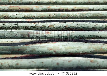 Old green metal bars close-up background. Geometrical pattern on a shabby vintage messy backdrop